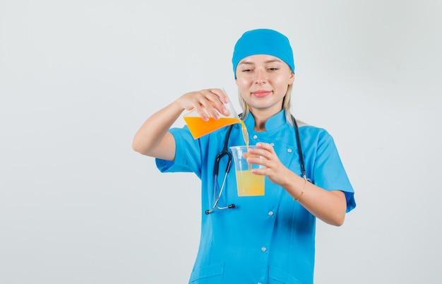 青い制服を着て笑顔でジュースを混ぜる女医