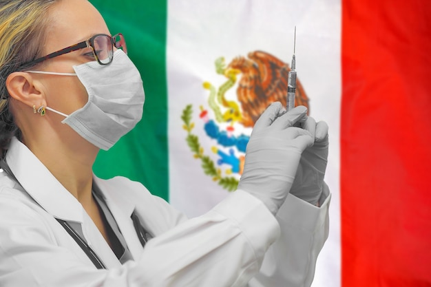 Female doctor or nurse in gloves holding syringe for vaccination against the mexico flag