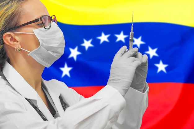 Female doctor or nurse in gloves holding syringe for vaccination against the venezuela flag