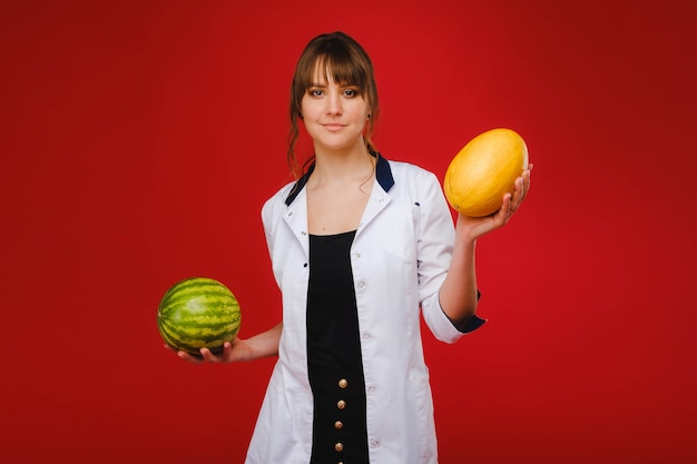 A female doctor nurse in a white coat with fruit in her hands poses on a red