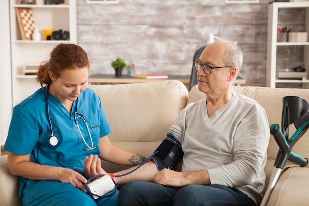 Medico femminile in casa di cura che controlla la pressione sanguigna dell'uomo anziano.