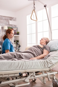 Female doctor in nursing home talking with senior woman with cancer.
