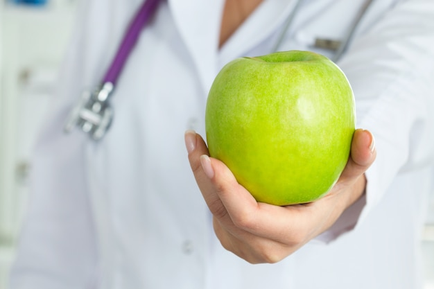 Female doctor offering green apple closeup