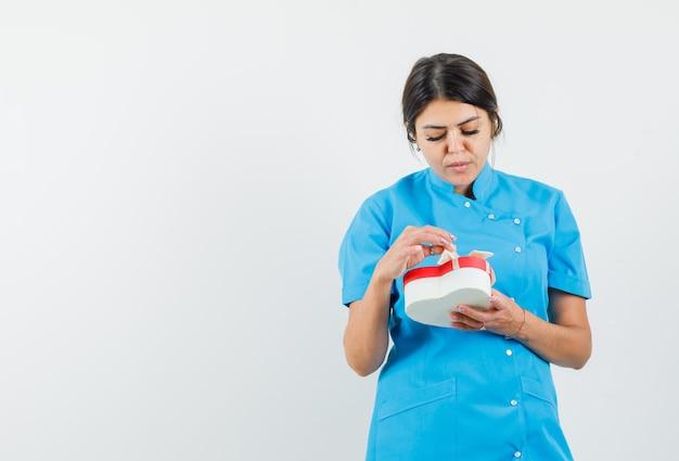 青い制服を着てプレゼントボックスを開けて落ち着いた女医師