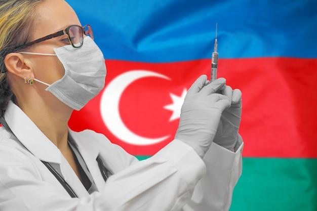 Женщина-врач или медсестра в перчатках держит шприц для вакцинации против флага азербайджана