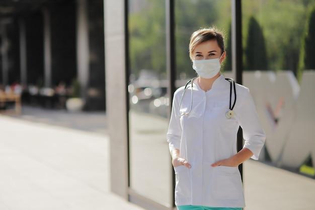 그녀의 목에 청진기로 보호 마스크를 착용하는 여성 의사 또는 간호사