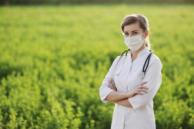 緑の草の背景に防護マスクを着ている女性医師や看護師