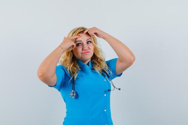 Женщина-врач щипает прыщи в синей форме