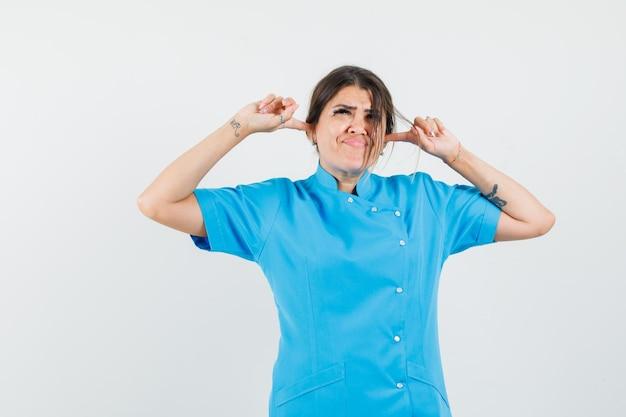 青い制服を着た指で耳をふさいでイライラしている女医