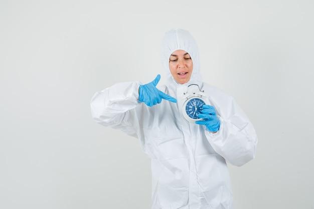 Женщина-врач, указывая на будильник в защитном костюме, перчатках и обнадеживая.