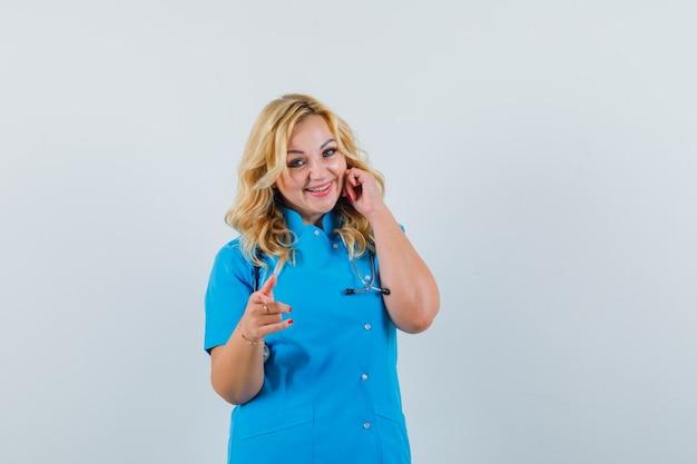 青い制服を着たカメラを指差して楽観的に見える女医。