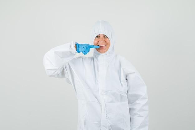 Женщина-врач, указывая на ее зубы в защитном костюме
