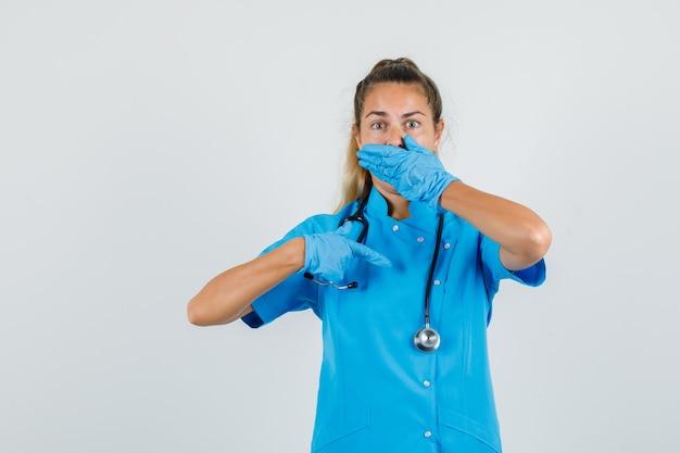 青い制服を着た女性医師が口に手を当てて自分を指しています