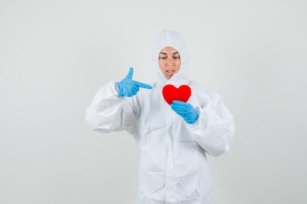 Женщина-врач, указывая на красное сердце в защитном костюме
