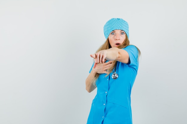Female doctor pointing away in blue uniform and looking puzzled