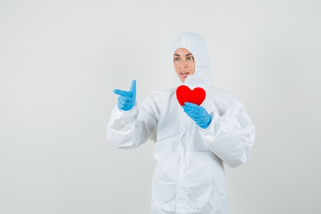 Female doctor pointing away while holding red heart in protective suit