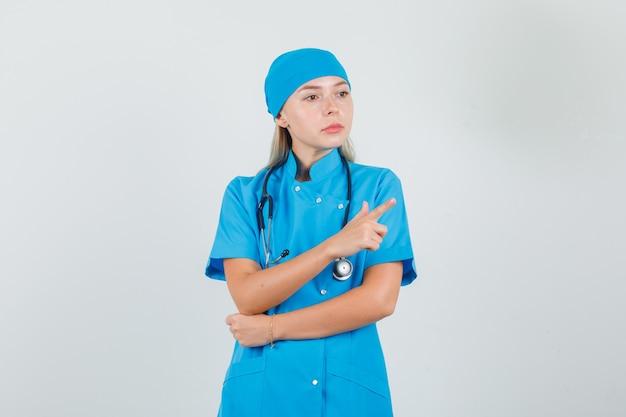 青い制服を着たまま脇を向いている女医師