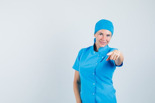 Medico femminile che indica alla macchina fotografica in uniforme blu e che sembra fiducioso. vista frontale.