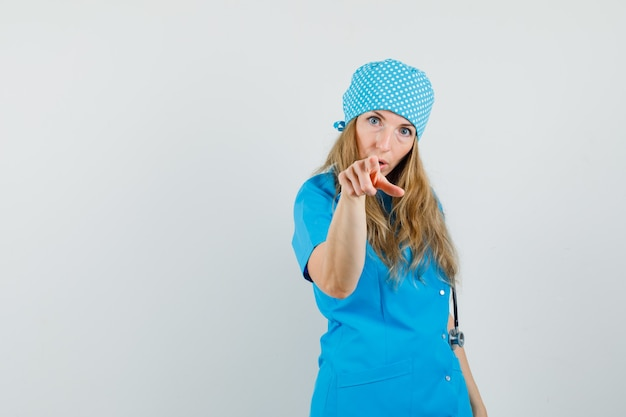 Female doctor pointing at camera in blue uniform and looking puzzled.