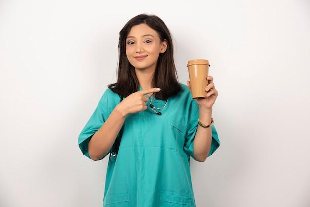 Женщина-врач указывая чашку кофе на белом фоне. фото высокого качества