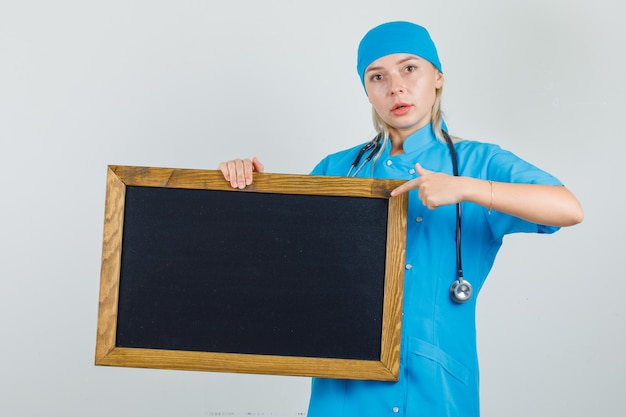 青い制服を着た黒板に指を指して真面目な女医師。