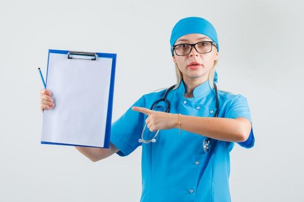 青い制服を着たクリップボードに指を指している女性医師