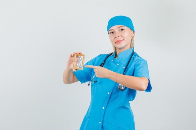 青い制服を着た砂時計に指を指し、陽気に見える女性医師。