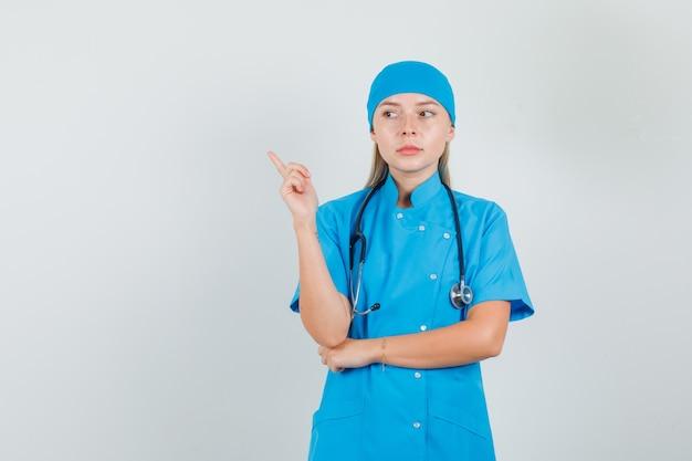 Medico donna che punta il dito lontano mentre pensa in uniforme blu