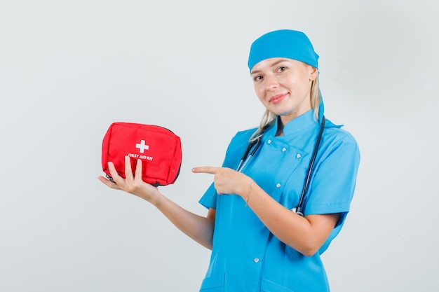 Female doctor pointing finger at first aid kit in blue uniform and looking cheerful.