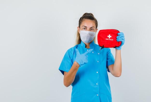 Dito puntato medico femminile al kit di pronto soccorso in uniforme blu