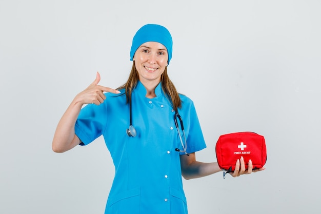 Female doctor pointing finger at first aid kit in uniform and looking cheery
