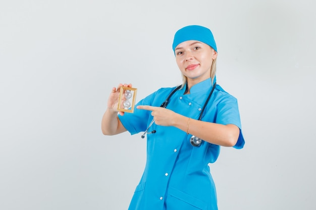 Female doctor pointing finger at hourglass in blue uniform and looking cheerful.