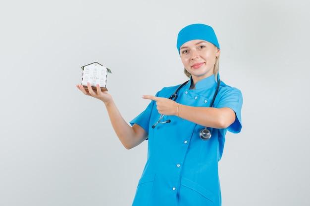 Dito puntato medico femminile al modello della casa in uniforme blu e che sembra allegro.