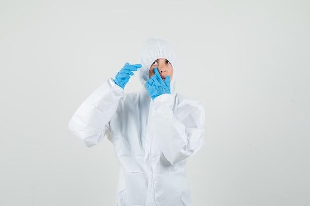 Medico femminile che indica alla sua palpebra tirata dal dito in tuta protettiva