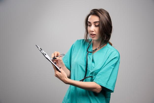 灰色の背景にメモを指す女性医師。高品質の写真