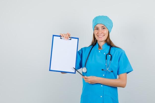 青い制服を着たクリップボードにペンを向けて喜んでいる女性医師。正面図。