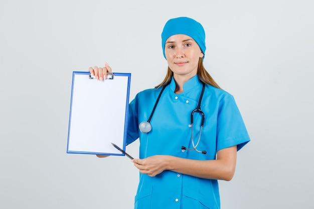 制服を着たクリップボードにペンを向けて、フレンドリーに見える女性医師。正面図。
