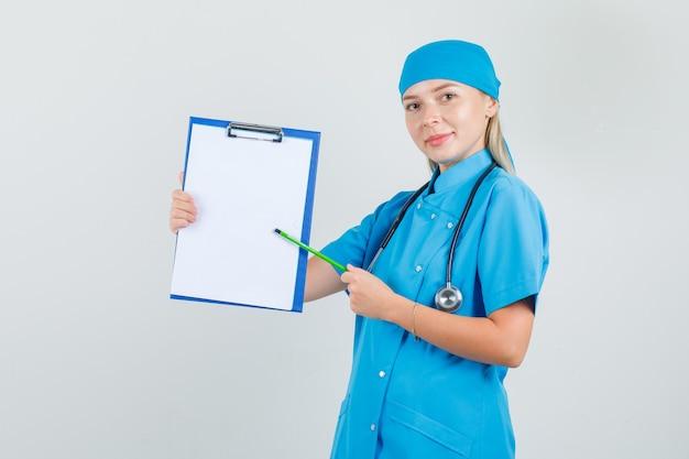 파란색 유니폼 클립 보드에 연필을 가리키고 쾌활한 찾고 여성 의사