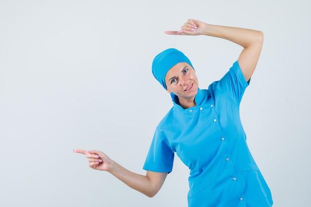 Medico femminile che indica il lato in uniforme blu e che sembra vivace. vista frontale.