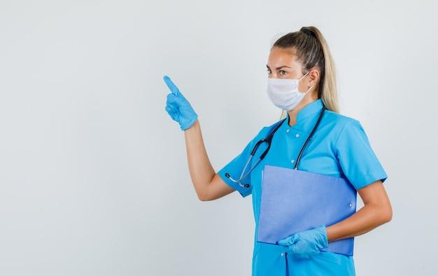 Женщина-врач, указывая в сторону, держа в руках буфер обмена в синей форме