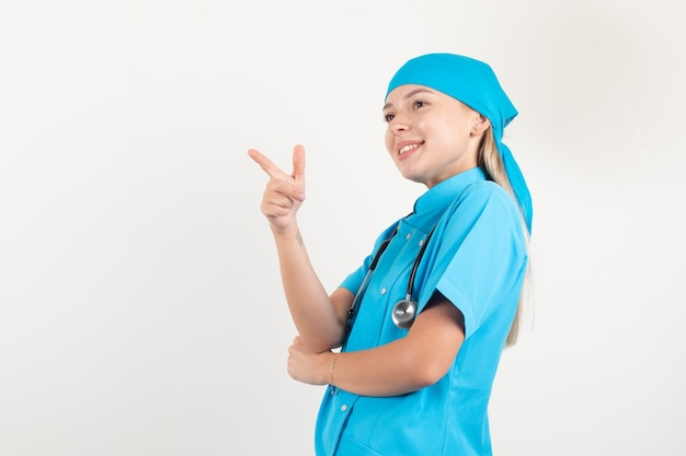 青い制服を着た銃のジェスチャーで横を指し、陽気に見える女性医師。