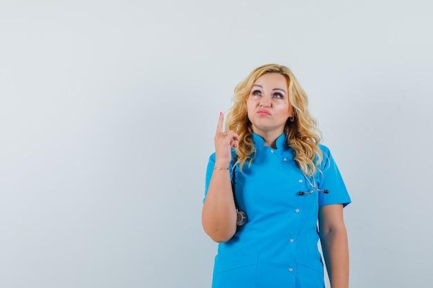青い制服を着た女性医師が不機嫌そうに見える。テキスト用のスペース