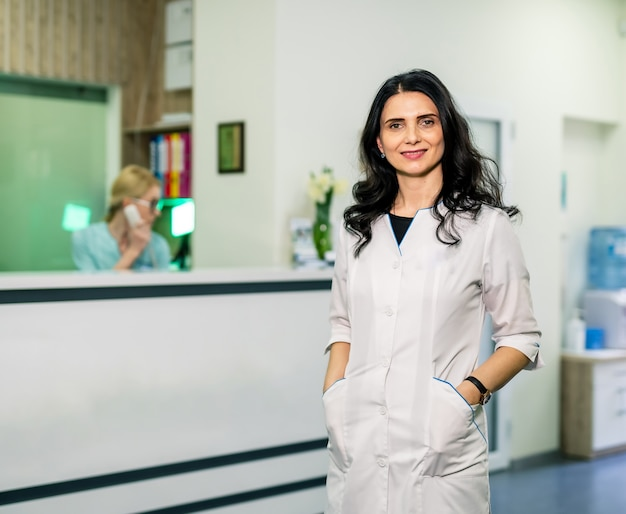 Female doctor posing near reception in hospital. woman in clinic.