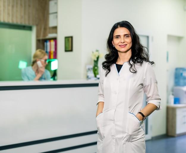 Женщина-врач позирует возле стойки регистрации в больнице. женщина в клинике.
