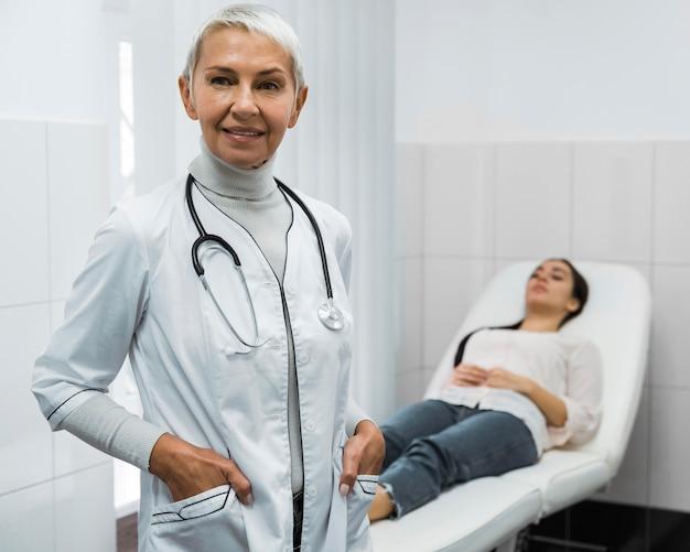患者の隣でポーズをとる女医師