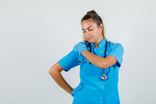 Female doctor posing while hands on shoulder and waist in blue uniform