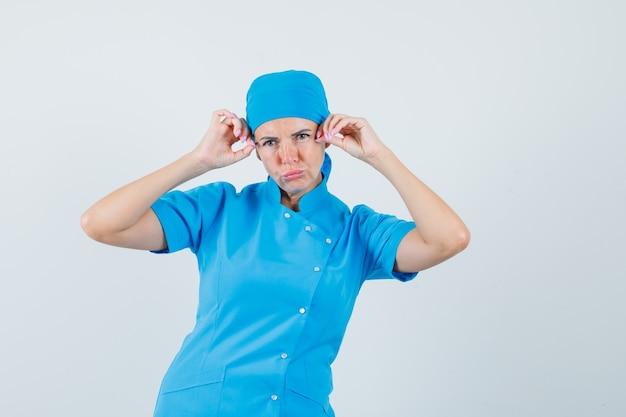 파란색 유니폼과 잠겨있는 찾고 머리에 손을 잡고 포즈를 취하는 여성 의사. 전면보기.