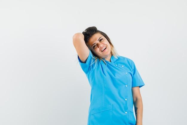 Женщина-врач позирует, держа поднятую руку над головой в синей форме