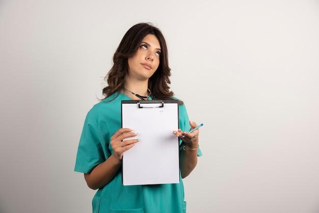白地にクリップボードでポーズをとる女医師