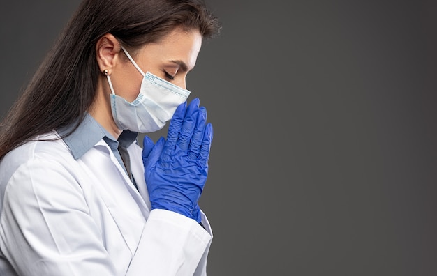 パンデミックの間に祈る女性医師
